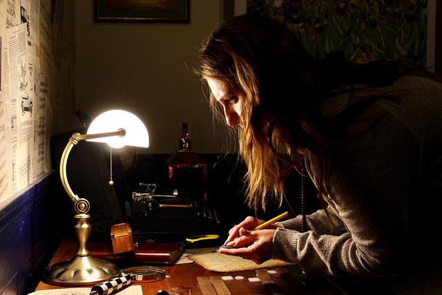 Femme qui recherche des indices sur un bureau pour résoudre une énigme