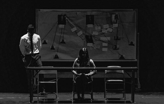 Personne assise dans une salle d'interrogatoire.